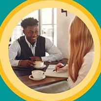 Two people in coffee shop talking.